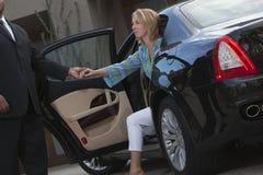 Fahrer-Hilfsfrau erhalten unten vom Auto Stockfotografie