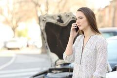 Fahrer mit aufgegliedertem Auto Versicherung am Telefon nennend lizenzfreies stockfoto