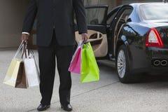 Fahrer mit Einkaufstaschen in der Fahrstraße Stockbild