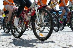 Fahrräder mit Füßen Leuten und Schatten auf Blöcken eines Steins, während eines Radrennens stockbild