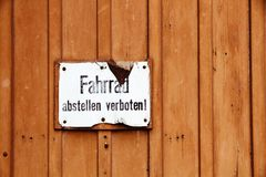 """Fahrrad abstellen verboten"" in German, parking of bicycles is prohibited old vintage cracked sign. Fixed to a brown wooden door Royalty Free Stock Photos"