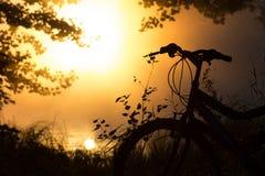 Fahrrad auf dem See vor der untergehenden Sonne Stockbild