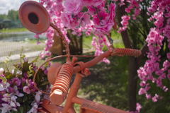 Fahrrad auf einem Hintergrund von rosa Blumen Lizenzfreies Stockfoto