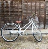 Fahrrad auf Weinleseholzhauswand Stockbild