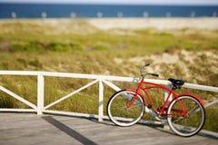 Fahrrad, das an der Schiene auf Strand sich lehnt. Stockfoto
