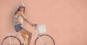 Fahrrad der jungen Frau Reitüber farbigem Hintergrund Stockbild