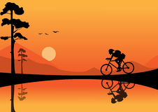 Fahrrad des jungen Mannes Reitauf Sonnenunterganghintergründen Stockfotos