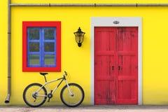 Fahrrad geparkt vor Retro- Weinlese-europäischem Wohnungsbau mit roter Tür, blauem Fenster und gelber Wand, schmales Straßenbild stock abbildung