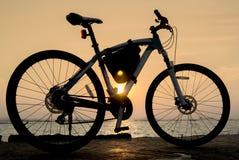Fahrrad mit Sonnenunterganghimmel Stockfotos