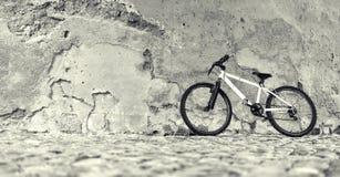 Fahrrad nahe einer Steinwand Stockfotos