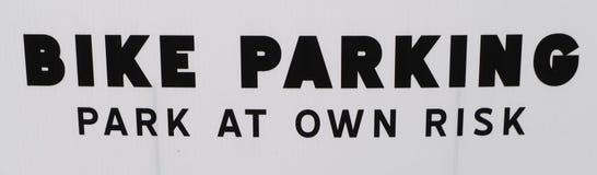FAHRRAD-PARKEN: PARKEN Sie AUF EIGENE GEFAHR das Zeichen, das nur um Radfahrer bittet zu parken lizenzfreie stockfotos