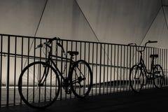 Fahrrad-Schattenbilder gegen Geländer nachts Stockfoto