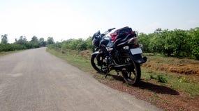 Fahrrad steht neben ländliches Gebiet-Straße Stockfotos