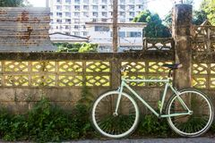Fahrrad und alter Zaunzement mit Wellblech das als der Hintergrund Lizenzfreie Stockfotografie