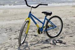 Fahrrad und Flipflops am Strand Stockbild