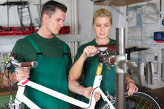 Fahrradmechaniker und -lehrling, die ein Fahrrad reparieren Stockfotografie