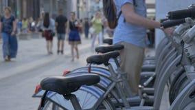 Fahrradparken nahe bei der Fußgängerstraße Leute gehen an einem Sommertag, nehmen ein Fahrrad in der Miete Gesunder Lebensstil stock footage