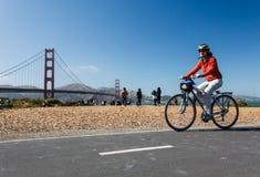 Fahrradreiter genießt sonniger Taggolden gate-Staatsangehörig-Erholungsgebiet Lizenzfreies Stockbild
