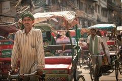 Fahrradrikscha, die das Fahrzeug auf die Straße von altem Delhi, Indien reitet stockfotos