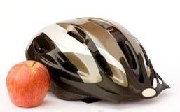 Fahrradsturzhelm und -apfel Stockfoto