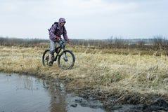 Fahrradtourist geht die überschwemmte Straße entlang Stockfotografie