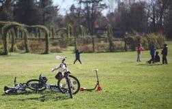 Fahrradwartezeit während Kinderspiel im Park lizenzfreie stockbilder