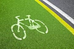 Fahrradweg - Fahrradschattenbild gezeichnet auf grünen Asphalt lizenzfreie stockbilder