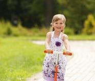 Fahrt des kleinen Mädchens der Roller im Park Lizenzfreies Stockfoto