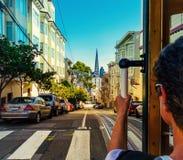 Fahrt mit der Drahtseilbahn in San Francisco Bild zeigt eine Person, die den berühmten STÄDTISCHEN Zug auf Powell-Maurerlinie rei lizenzfreie stockfotografie