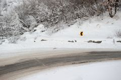Fahrweg auf Hügel mit gefrorenen Niederlassungen und Schnee fällt Stockfotografie