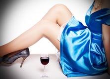 Fahrwerkbeine in den Schuhen und in einem Glas roten wi Stockfotografie