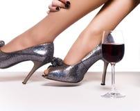 Fahrwerkbeine in den Schuhen und in einem Glas roten wi Stockfotos