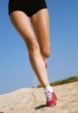 Fahrwerkbeine der Frau laufend auf Sand Stockbild