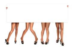 Fahrwerkbeine der Frauen, die ein unbelegtes Zeichen halten Stockfotografie