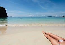 Fahrwerkbeine der jungen Frau auf dem Strand Lizenzfreie Stockbilder