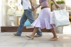 Fahrwerkbeine des Paares mit dem Einkaufen Stockfotos