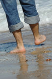 Fahrwerkbeine eines Mannes, der auf den Strand geht Lizenzfreie Stockfotos