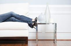 Fahrwerkbeines der Frau, das auf weiße Couch stützt lizenzfreie stockbilder