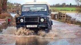 Fahrzeug-Fahren durch Hochwasser auf Straße stockfotografie