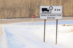 Fahrzeug-Inspektions-voran Zeichen mit Landstraße im Hintergrund Stockbilder