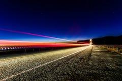 Fahrzeug-Licht-Spuren auf Landstraße Stockfotografie