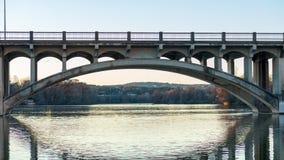 Fahrzeug und Fußgängerübergangbrücke, die über einem Fluss während der goldenen Stunde überspannt lizenzfreie stockfotografie