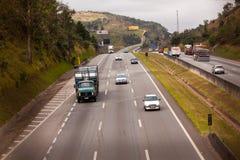 Fahrzeuge auf Landstraße BR-374 mit Scheinwerfern an während des Tageslichts die neuen brasilianischen Durchfahrtgesetze befolgen stockfotografie