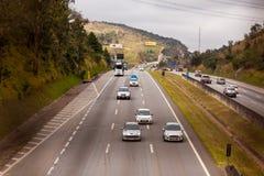 Fahrzeuge auf Landstraße BR-374 mit Scheinwerfern an während des Tageslichts die neuen brasilianischen Durchfahrtgesetze befolgen lizenzfreie stockfotografie