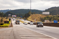 Fahrzeuge auf Landstraße BR-374 mit Scheinwerfern an während des Tageslichts die neuen brasilianischen Durchfahrtgesetze befolgen stockbild