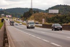 Fahrzeuge auf Landstraße BR-374 mit Scheinwerfern an während des Tageslichts die neuen brasilianischen Durchfahrtgesetze befolgen stockfoto