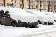 Fahrzeuge bedeckt mit Schnee im Winterblizzard im Parken Lizenzfreie Stockfotografie