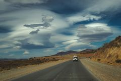 Fahrzeugfahren auf eine Teerstraße durch Wüste stockfotografie