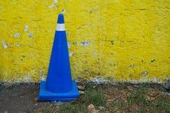 Fahrzeugsteuerkegel in der Königsblaufarbe gegen eine gelbe Wand lizenzfreie stockfotografie