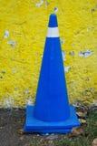 Fahrzeugsteuerkegel in der Königsblaufarbe gegen eine gelbe Wand lizenzfreies stockfoto
